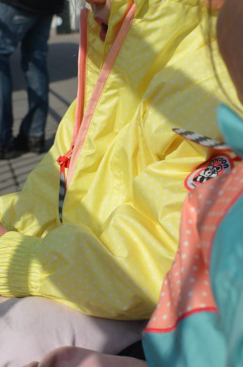 Hattaralla on keltainen, valkopilkullinen anorakki malli. Vuori on vaaleanpunainen.